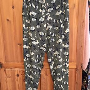 Brand: John Rocha Varetype: Lækre tynde sommerbukser Størrelse: 20 (46-48) Farve: Armygrøn  Lette løse bukser med elastik og bindebånd i talje. Lige ben.    Lille opslag forneden på ben.  Blomster på armygrøn baggrund.   Polyester med 7% elastan.     Bukserne er nye og afprøvet en gang.    Prisen er fast: 200 kr. inkl. porto med DAO.
