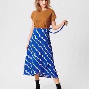 """Helt ny """"slå om"""" nederdel fra Moss Copenhagen str. XS (passes også af en small)   Har fortrudt købet og nåede ikke at bytte den. Prisskilt sidder stadig på."""