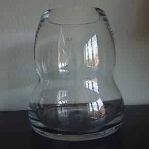 Glas, Meget stor gulvvase, Gracius Gracius Gulvvasen af Knud Holscher, Holmegaard  Højde 30cm. Ø 26.4cm  Vasen er lavet i 3 størrelser. Dette er den største model.  Den er utrolig smuk med lys I. Men kan selvfølgelig også anvendes traditionelt som vase og gulvvase.  2 stk haves. Begge uden glaspest, kalk mv. De har stået på gulvet op ad terrassedørene med netop lys i, og har derfor en tynd cirkel af brugsridser under bunden.  1 stk fejlfri . Pris 550kr  1 stk med flad flig slået af i toppen. Dette skæmme dog ikke. Pris 350 kr.  Befinder sig i Kbh S.  Udbringning i Storkøbenhavn kan evt arrangeres. Kan også sendes. (Køber betaler porto, sælger betaler for forsvarlig indpakning). Vær dog opmærksom på, at vasen er stor, solid og derfor tung