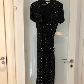 Flot lang slå-om kjole med bindebånd. Sort bund med råhvide prikker. Brugt to gange. Den kan hentes på Islands brygge eller sendes på købers regning.
