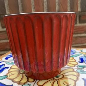 Rød retro keramik urtepotte fra West-Germany 2/2. Potten er fin og uden skår, dog med brugsspor indvendigt. Højde 12,5 cm og diameter 14 cm. Sendes mod betaling af porto.