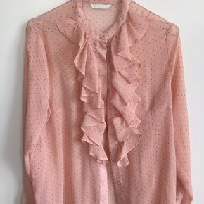 Sød skjorte med flæse i gennemsigtig chiffon. Fersken/lyserød med sorte prikker.