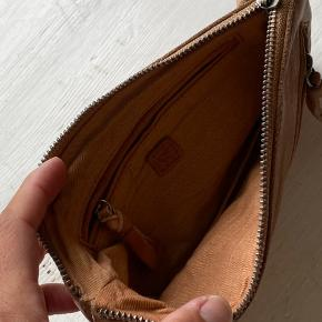 Cognacfarvet kærnelæderpung med diagonal lynlås. Indvendigt lomme med lynlås og pænt for. Måler 12 cm • 21 cm. Næsten som ny