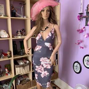 Helt ny kjole( har ingen mærke på) Super flot elastik strop lysgrå kjole m/ gammelrosa farvet blomster på. Nedskæring foran og barryg. Påsyet gråt skørt under kjolen.  Str : S  Mærke : Shein   95% polyester  5% spandex