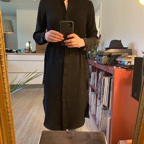 Lang skjørte kjole med løbegang i taljen, således at man kan tage den ind i taljen eller bære den mere oversize. Kan bruges lukket og åben til bukser