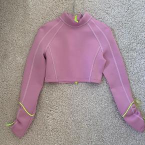 Prisen er fast, bud frabedes.  Rosa/lyserød trøje i glat scuba stof. Stretchy med neongule detaljer. Jeg er str 36/s standard.  Nypris 349, købt nedsat til 249,- sidste år