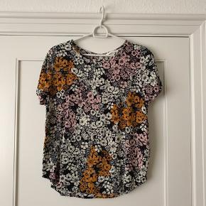 Blomstret top/t-shirt. Der står 44 i den men er nærmere en 40/42. Du er altid velkommen til at prøve inden et evt. køb