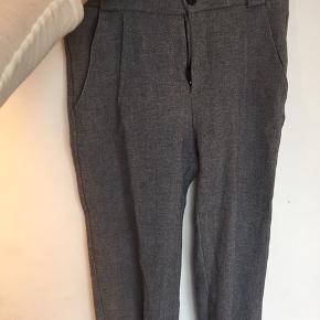Løse bukser som er brugt, men stadig er pæne. Der er et hul i den ene forrest lomme, som efterfølgende er syet sammen igen.