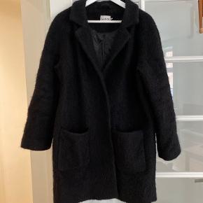 45% uld - 55% polyester.  Frakken er i fin stand, brugt en enkelt sæson. Bælte stropperne er gået løs i begge sider (sidste billede), men kan sagtens syes på, eller klippes helt af. Jeg har brugt frakken uden bælte.
