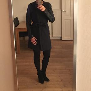 Flot uldfrakke med ærmer af ægte læder i en meget mørkeblå (næsten sort) farve. Kan både bruges til en str. m og s.