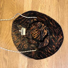 Bøllehat i regntøjsstof fra Ganni i leopard lignende mønster. Hatten er brugt meget få gange og fremstår derfor som ny. Hatten er onesize.