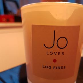 70g Aldrig brugt Stadig med folie på toppen.  https://www.youtube.com/watch?v=FYVtLEWResI  Come in from the cold and enjoy the heady, sophisticated scent of Jo Loves Log Fires A Scented Candle, a gorgeous fragranced candle that blends smoky woods and Lapsang Souchong tea to invoke happy memories of evenings spent beside a roaring hearth. Hand poured and crafted in England, this candle is inspired by the warming, familiar fragrance of a roaring log fire 🔥  Its notes promise to calm, soothe and embrace those who have come in from the cold.  Stay warm and snug inside, regardless of the weather, with Jo Loves Log Fires A Scented Candle, a fragranced candle that warms and inspires.  Key Benefits: Hand poured and crafted in England Ideal as a gift Notes of smoky wood and Lapsang and Souchong tea Inspired by the scent of a roaring log fire