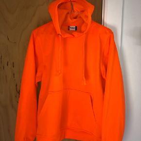 Neon orange bluse som er brugt godt, men står stadig pænt. Snorene i hætten har dog tråde, som har bevæget sig. Se sidste billede