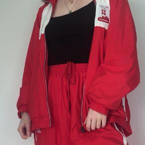 Super fed vintage Adidas-jakke til dit sporty/athleisure look! 🏃♀️🏃♂️  Originalt en del af et sæt fra Danmarksholdet i OL 2000 i Sydney. (Tjek andet opslag) ❤️🇩🇰  Jakken er rød og hvid med Adidas og OL-logoet foran og er elastisk om ærmerne og for neden. 🛀  Mega fedt sporty vintage look som kommer til at gøre alle dine venner misundelige! 🛍  Str. L-XL herrer, men er unisex og kan passes af XS-XL alt efter ønsket pasform (oversize/ikke oversize).  Skriv endelig, hvis du ønsker ekstra info eller billeder! 🌸