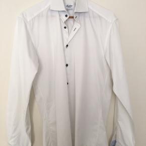 Hvid fitted body skjorte fra Stenstrøms str. 39. Lyseblå kant indeni manchetter og krave og grøn tråd i knaphuller og knapper.  Skjorten er kun brugt enkelte gange. Der er nogle små pletter helt nede ved skjortekanten på ryggen, de ses ikke når skjorten er nede i bukserne.  Nypris 1300kr. Afhentes i Gentofte eller sendes på købers regning.
