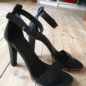 Høje sandaler fra COS i sort læder i str. 38. Nypris 1200 kr. Brugt et par gange, men i god stand.
