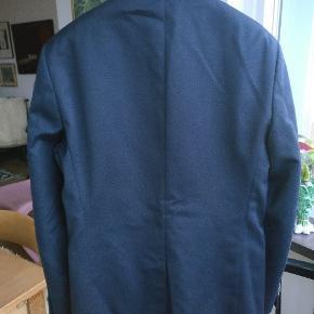 Flot mørkeblå blazer med et par sjove deltager, blandt andet de flotte knapper. Lavet i et blandingsmateriale og str. er 48, en regulær pasform og passer nok en M bedst.