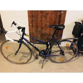 MBK racer Bike fra 90'erne. En dame model i rigtig fin stand. Købte den selv af en som havde sat den totalt i stand, så den kører som en drøm og gearene glider let. Original sadel. Den trænger dog til nye dæk inden længe.