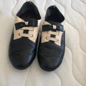 Fine sko sælges, købt secondhand i New York. En kombination af lak og læder. Fin stand, men naturlige brugsspor må forventes. Der står størrelse 38 i skoene, men de er små (!) i størrelsen og passer derfor en alm. 37.