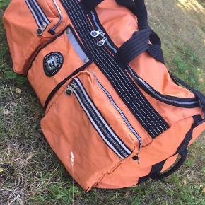Sjælden super cool orange rejsetaske / weekendtaske i PVC og nylon designet af  ESPRIT.  Tasken fremstår med meget få brugsspor uden slid, huller eller misfarvninger.  Tasken har: 4 frontlommer 1 værdilomme med trykknapper  Stærke maxi lynlåse til hængelås Kraftig skulderrem Kraftig og behagelige håndtag med trykknapper.  Bredde: 68 cm Dybde: 25 cm Højde: 37 cm Front lommer: 24 x 22 cm