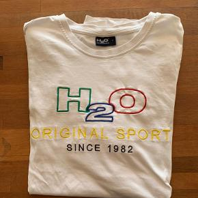 T-Shirt med logo foran fra H2O. Størrelsen er en small men den kan sagtens passe en medium🤍