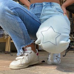 Super fede jeans fra H&M med søde stjerner på knæene. Har selv i karantænen afbleget den ene halvdel af bukserne, sådan så bukserne får en fed effekt med to forskellige farver. Bukserne er i en 36 men har selv syet dem ind i taljen så de sad til, derfor  passer de også en 34.