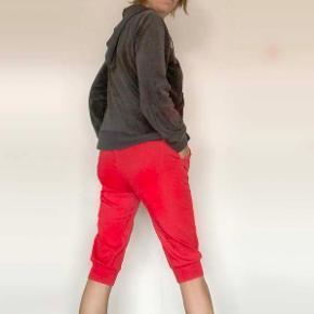 3/4-lange bukser / knickers / capri  Røde bukser i bomuldslærred. Elastik og ribkant i taljen. Ribkant nederst på benene. Stiklommer foran med pynt i kanten.  Størrelse M, ustrukket måler ribkanten øverst 70 cm, kan strækkes til mindst 95 cm. Indvendig benlængde ca. 50 cm.  Har været brugt og vasket en enkelt gang, så bukserne fremstår som nye.  Sælges for kun 35 kr. + evt. porto.  Kan afhentes på Frederiksberg.