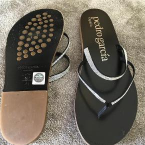 Varetype: Sandaler/klip klapper Farve: Sort Oprindelig købspris: 2200 kr. Prisen angivet er inklusiv forsendelse.  Billedet siger sig selv - super smuk og lækker sandal med swarovski krystaller. Brugt 2 gange