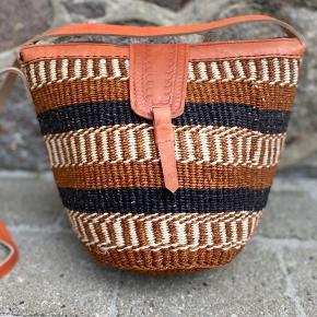 Smuk, håndlavet sisaltaske med detaljer af ægte læder. Læderremmen kan justeres til den ønskede længde. Åbningen på tasken er ca. 32 cm. Den er foret indvendigt og der er lynlås i toppen.   Se flere tasker på min profil i forskellige designs og størrelse.   Taskerne er købt på lokale markeder i Kenya.  Varen kan sendes med DAO eller afhentes efter aftale.   # Crossbody taske, Afrika, Kenya, sisal, unik
