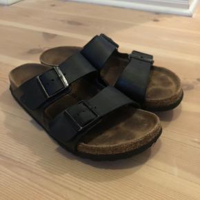Birkenstock sandaler i sort. Godt brugt, men det er jo en holdbar sandal. De er revnet lidt fra der, hvor tæerne bøjer (hvilket fremgår af et af billederne) men ellers er der kun det slid som ses på de andre billeder.