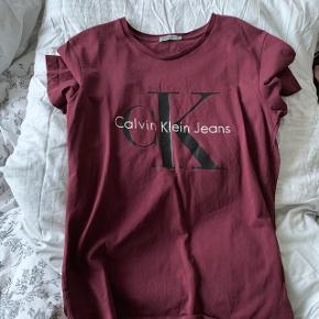 Calvin Klein tee i Bodo rød bordeaux rød.Str L, den fitter M Sælger den da den er for stor Aldrig brugt, kun prøvet på!