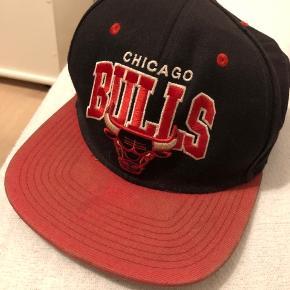 Chicago Bulls cap i sort og rød fra mærket Mitchel & Ness.  Kasketten er brugt en del, som også kan ses på billederne. Condition 3-4/10. Derfor den lave pris.  Bud modtages  Eventuel fragt er på købers regning.