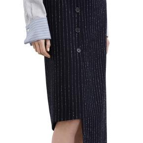 Asymmetrisk nederdel med knappelukning. Har inderfoer, så uldkvaliteten ikke irriterer mod huden