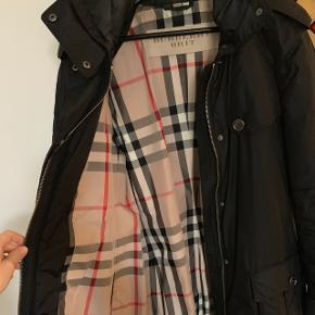 Super lækker og varm lang jakke. Sort med mange detaljer. Foer i Burberry stof. Skjult hætte i kraven. Bælte med logo på spændet. Skriv for flere billeder!