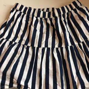 Sød lille nederdel med mørkeblå/ råhvide striber str 122/128.  Har justerbar elastik i taljen. Afh i 6710