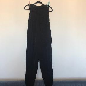 Just Female buksedragt, med løs og lav harems agtig bukse del.  Lukkes med lynlås i siden. Flot feminin i toppen.  Med leo print inspireret mønster. Der er shine i den sorte tråd.