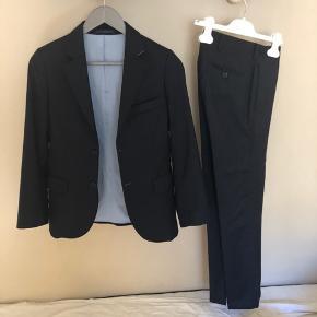 Det flotteste jakkesæt til teenageren. Det har en anelse shine effekt. Det er den lækreste kvalitet der falder utrolig flot. Nyprisen var over 2500kr