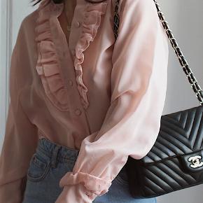 Så smuk fransk vintage bluse fra 1990'erne med de fineste detaljer sælges. Skjorten har en lille reperation nederst ved det ene ærme (se billede to) - ikke noget der bemærkes, men skal selvfølgelig nævnes: ellers er standen god.