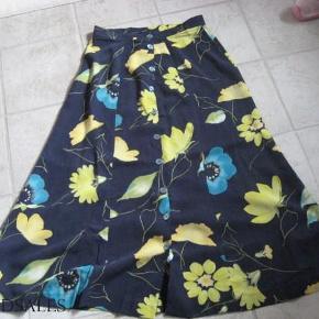 Flot lang nederdel (90 cm) i mikrofiberstof - føles som silke. Knapper hele vejen ned foran.  Måler ca. 69 cm i taljen - men øverste knap kan flyttes ind - og dermed også passe af lidt mindre taljemål.  Se også mine andre annoncer.  Klassisk nederdel - sommernederdel Farve: Blå