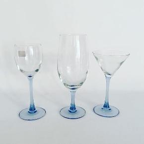 Franske vintage glas med blå fod. Der er 8 ølglas, 3  hvidvinsglas og 10 cocktailglas. Ølglassene måler: H: 21 cm. Hvidvinsglassene måler: H: 19 cm. Cocktailglassene måler: H: 16,5 cm. Glassene koster 25 kr. pr. stk. #luminarc #franskeglas #cocktailglas #drinksglas #hvidvinsglas #glaspåblåfod #vintageglas #retroglas