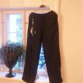 Sorte bukser fra Ilaria Nistri i italiensk str 44, passer til dansk str. 40  I en hørblanding med elastik og løbegang i taljen, lommer i siderne og ellers ganske enkle.  Stadig med mærke og aldrig brugt