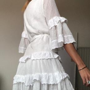 Fin hvid kjole med bånd og blonder. Fejler intet, da den kun er brugt en gang.