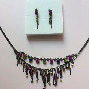 Smykkesæt bestående af halskæde og øreringe i et antikt guldlook. Kæden kan blive op til 43 cm lang og øreringene er 4 cm lange.