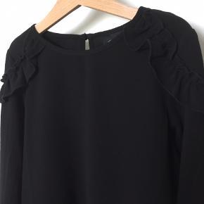 Skøn bluse fra Petit by Sofie Schnoor med fine detaljer på skuldrene.  Denne har kun været vasket en enkelt gang.