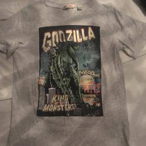 """Super fed """"Godzilla"""" t-shirt i grå med print. Str S mener jeg, lidt lille i størrelsen. Aldrig brugt.   Nypris omkring 100 kr.  Hvis den skal sendes, betaler køber fragt.  Mvh Betina Thy"""