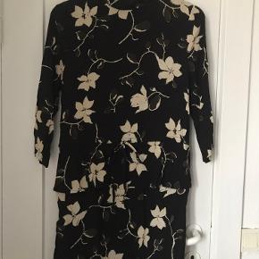 Kort sort/hvid mønstret kjole fra Ganni. Høj hals, lange ærmer med ly lås bagpå. Kan bindes i/strammes i taljen.  Sender ikke - alt kan hentes på Emdrup st. i København.