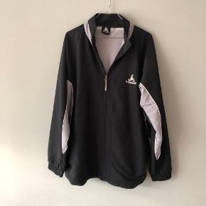 Fed og lækker langærmet tracktop jakke fra Le Coq Sportif  Jakken har 2 lommer foran på jakken og der er mulighed for at stramme jakken ind   Størrelsen er M   Kan afhentes i Århus C eller sendes på købers regning :)