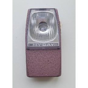 """Ældre """"spejderlygte"""" med krog bagpå der kan slåes op eller ned, så den kan hænge. Har lille pære inden, men mangler batteri. Ved desværre ikke om den virker, men den er så dekorativ. Fineste rosa-metallic farve. Måler 12,5x7cm."""