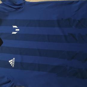 Varetype: T-shirt Farve: Blå Prisen angivet er inklusiv forsendelse.  Der er løbet en lille tråd i halsen, ellers nsn-kan evt følge med billigt i en handel