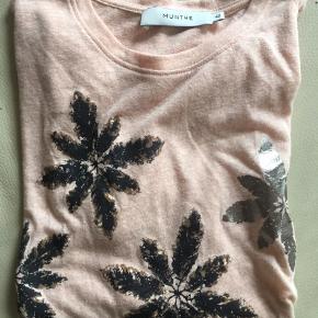 Smuk T-shirt i pudder/lys laksefarve. Blomsterne på er sort/brune og sølv. Blød og lækker kvalitet Nypris: 600